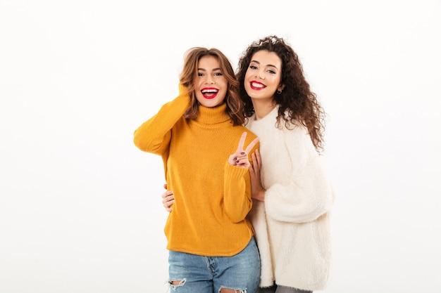 Twee glimlachende meisjes in sweaters die samen stellen terwijl één vrouw die vredesgebaar over witte muur tonen