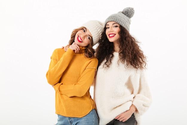 Twee glimlachende meisjes in sweaters en hoeden die samen over witte muur stellen