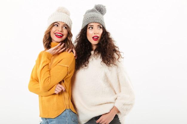 Twee glimlachende meisjes in sweaters en hoeden die zich terwijl het kijken weg over witte muur verenigen