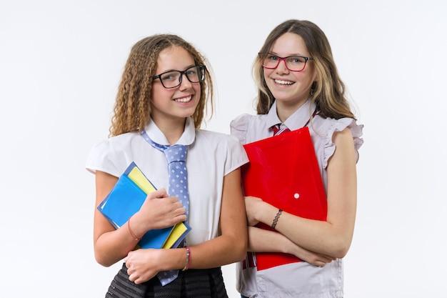Twee glimlachende middelbare schoolmeisjes die op witte achtergrond stellen