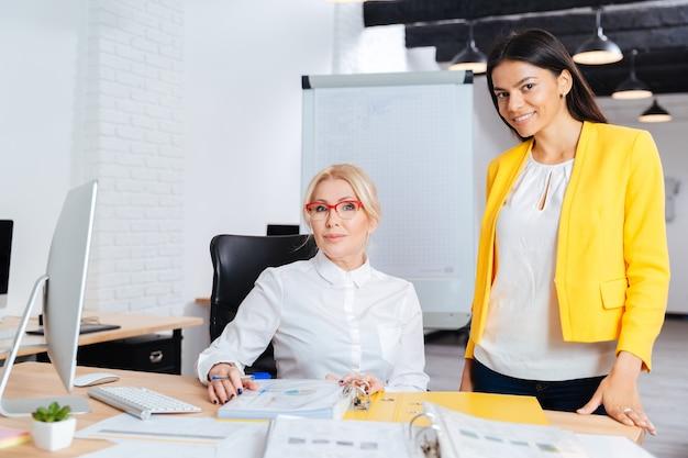 Twee glimlachende ondernemers werken samen op de computer aan de tafel in het kantoor