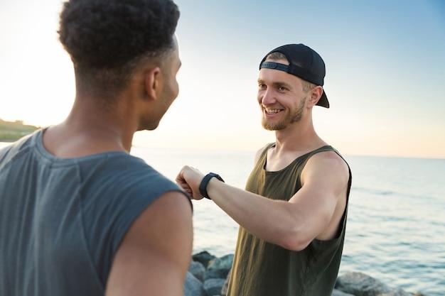 Twee glimlachende sportmannen die na het runnen van training rusten