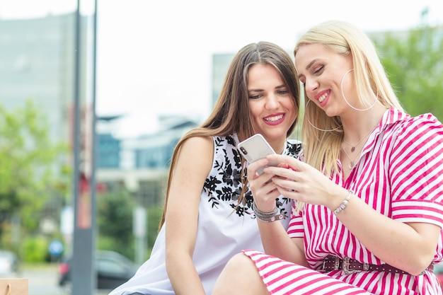 Twee glimlachende vrouwelijke vrienden die mobiele telefoon bekijken