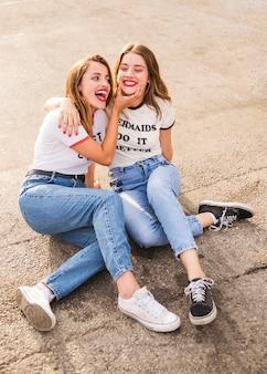 Twee glimlachende vrouwelijke vrienden die op bestrating zitten