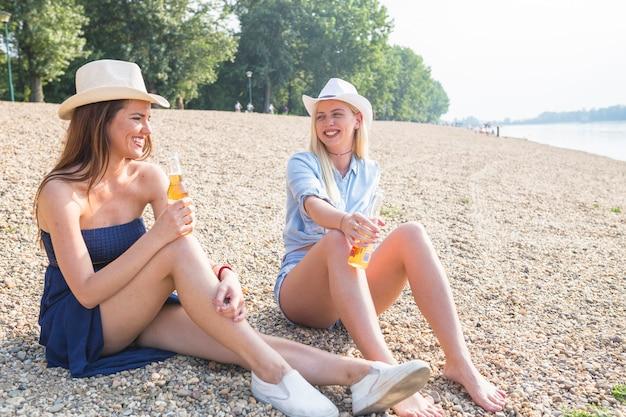 Twee glimlachende vrouwelijke vrienden die op strand het drinken fruitbier zitten