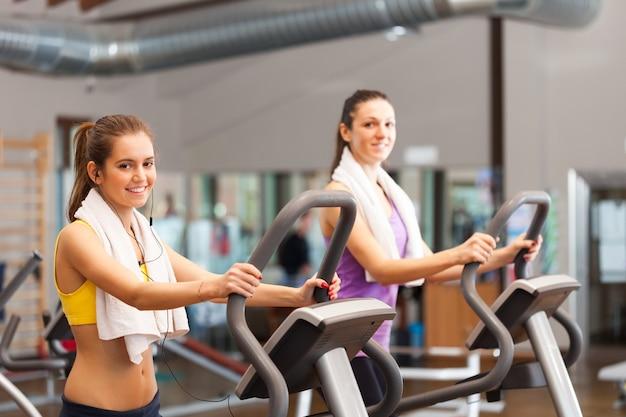 Twee glimlachende vrouwen die in een gymnastiek uitwerken