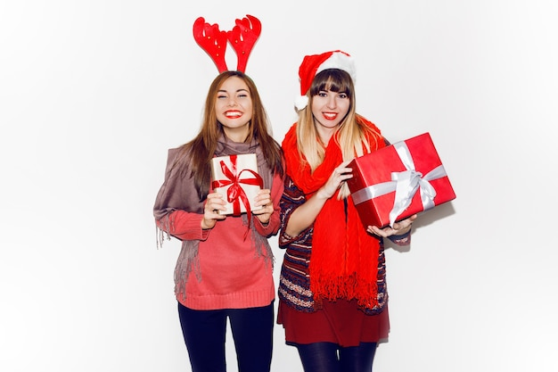 Twee glimlachende vrouwen die nieuwe jaargiften houden. het dragen van schattige maskeradehoeden. openhartige glimlach. feeststemming. flash portret.