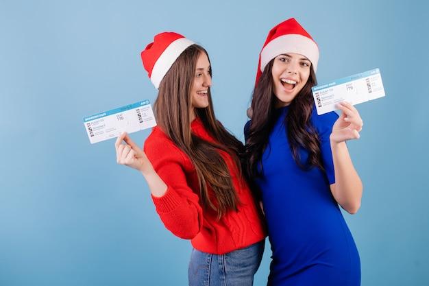 Twee glimlachende vrouwen die santahoeden met vliegtuigkaartjes dragen die over blauw worden geïsoleerd