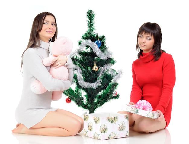 Twee glimlachende vrouwen poseren naast een kerstboom en een cadeau. het meisje houdt handen dichtbij het gezicht. lichte muur