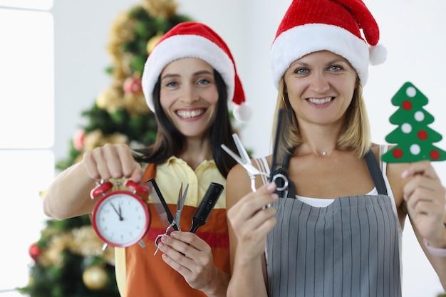 Twee glimlachende vrouwenkappers in uniformen en kerstmanhoeden houden een wekkerschaar met kam vast.