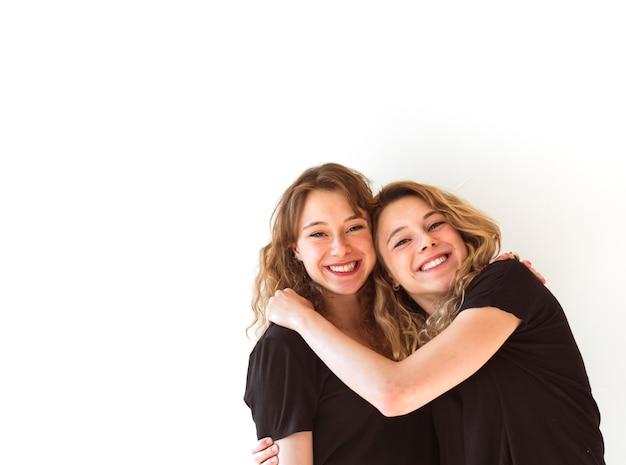 Twee glimlachende zusters die op witte achtergrond omhelzen