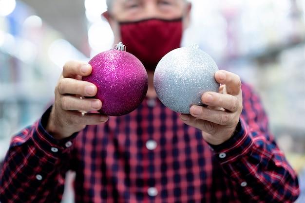 Twee glinsterende kerstballen, zilver en paars, in de handen van een oude man met een medisch masker als gevolg van een coronavirusinfectie