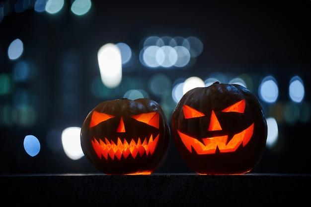 Twee gloeiende halloween-pompoenen in de stad bij nacht