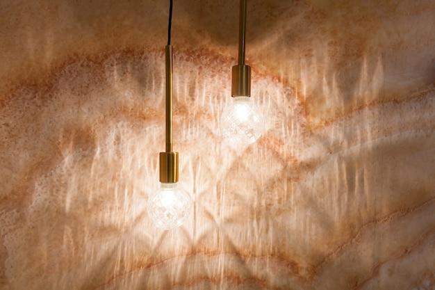 Twee gloeilampen die op een achtergrond van een beige muur hangen. lampen op de achtergrond van een beige muur.