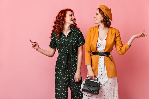 Twee goedgehumeurde dames kijken elkaar aan. studio shot van verfijnde meisjes praten op roze achtergrond.