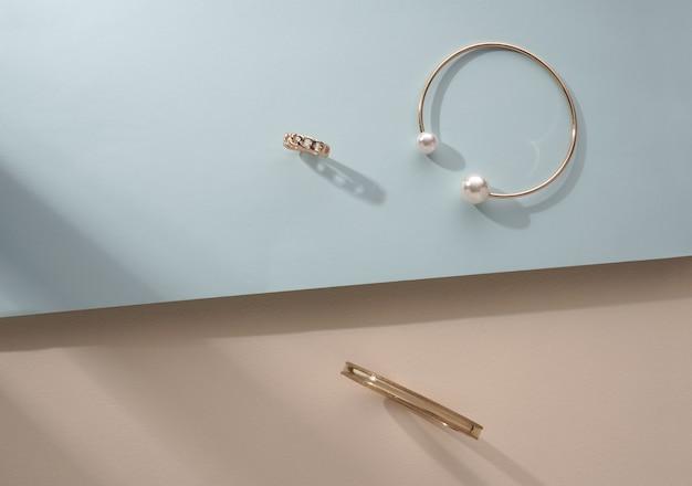 Twee gouden armband en ring op beige en blauwe achtergrond met kopie ruimte