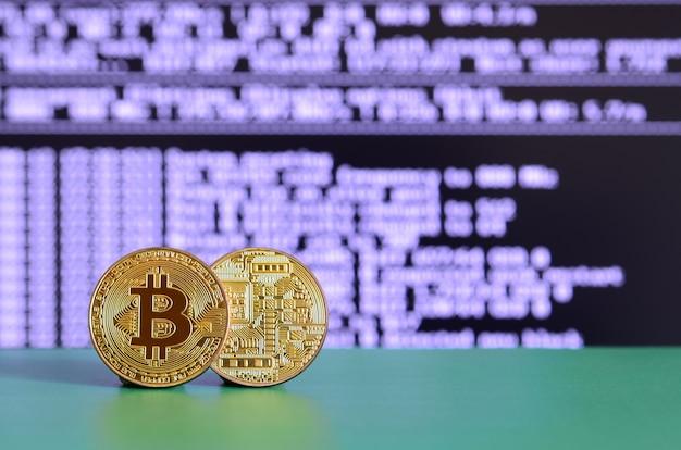 Twee gouden bitcoins liggen op het groene oppervlak op de achtergrond van het scherm