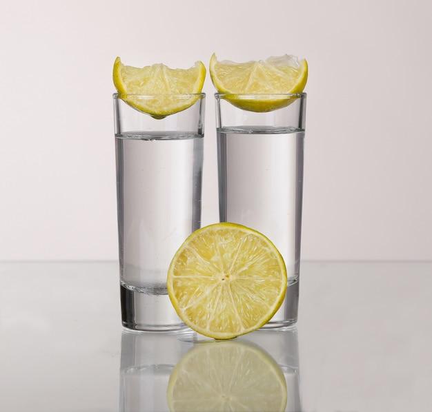 Twee gouden tequilaschoten met limoen geïsoleerd op een witte achtergrond