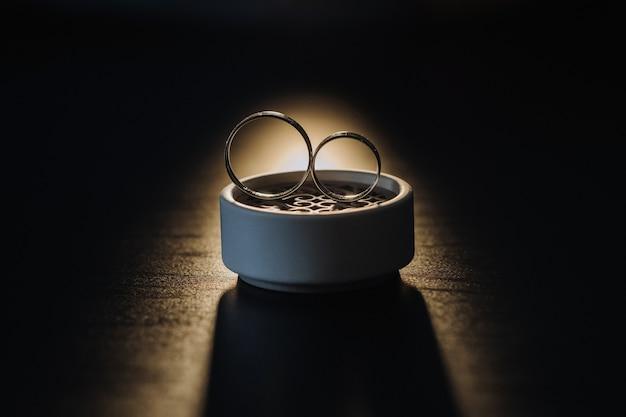 Twee gouden trouwringen in een witte doos op een zwarte achtergrond