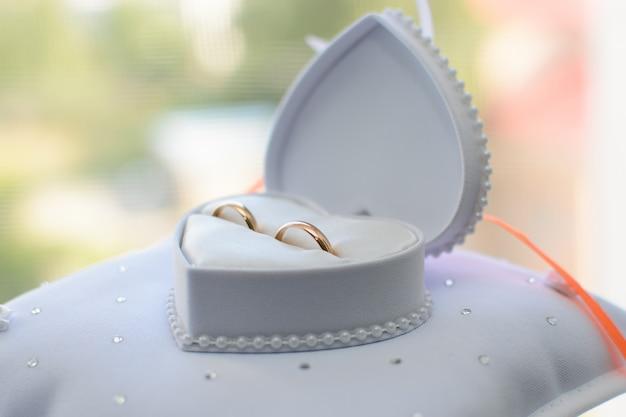 Twee gouden trouwringen liggen in een witte doos