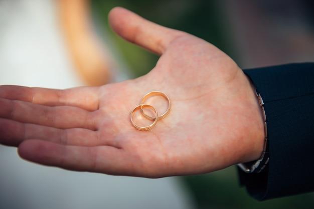 Twee gouden trouwringen liggen op de open handpalm van een man