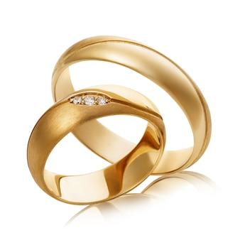 Twee gouden trouwringen met diamanten op wit wordt geïsoleerd