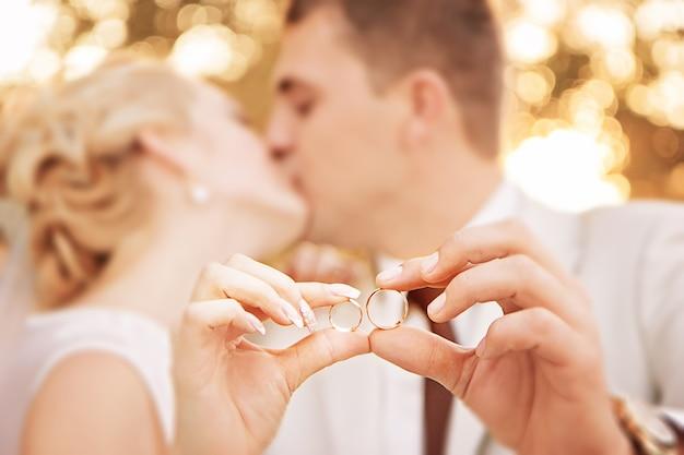 Twee gouden trouwringen op armen van kussende pasgetrouwden. kleine scherptediepte.