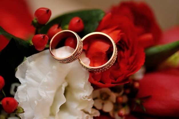 Twee gouden trouwringen op bruidboeket van rozen