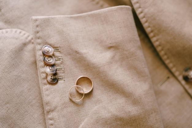Twee gouden trouwringen op de mouw van een beige herenjasje met knoopjes