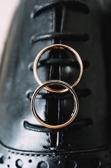 Twee gouden trouwringen op een achtergrond van zwarte herenschoenen met vetersluiting