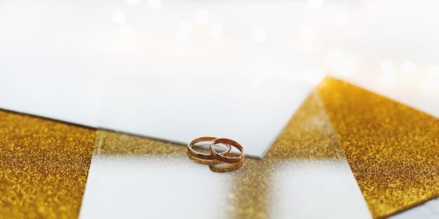 Twee gouden trouwringen op een gouden achtergrond.