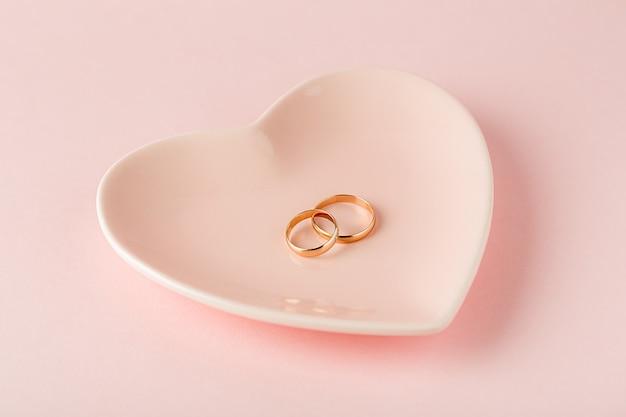 Twee gouden trouwringen op een roze plaatje in de vorm van een hart op een roze achtergrond