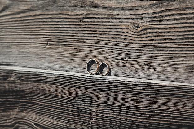 Twee gouden trouwringen op een stuk hout.