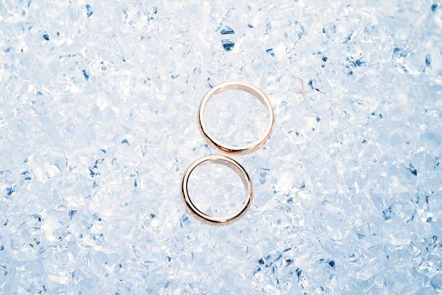 Twee gouden trouwringen op ijs.