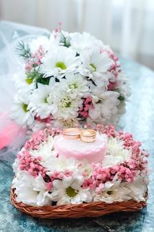 Twee gouden trouwringen op mooi wit en roze boeket in rustieke mandenmakerij. sluit omhoog.
