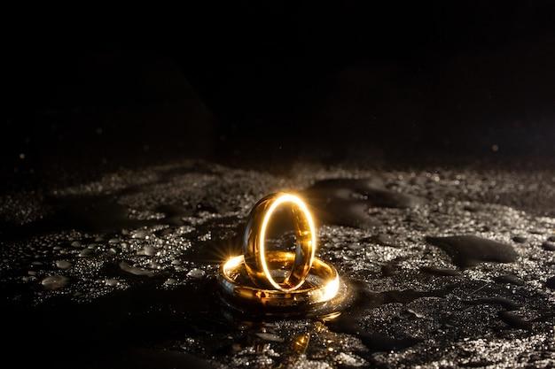 Twee gouden trouwringen op zwarte achtergrond.