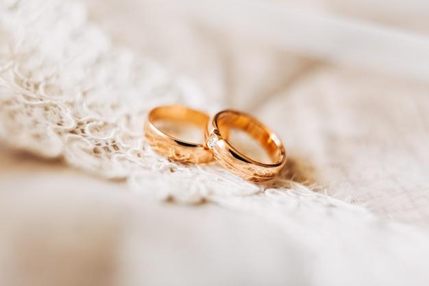 Twee gouden trouwringen voor de bruid en bruidegom met een edelsteen op wit kant