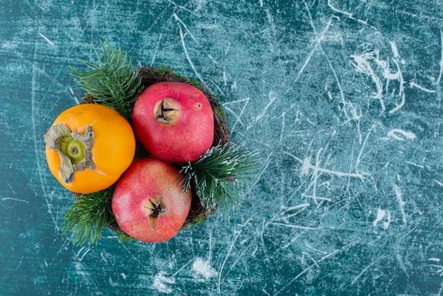 Twee granaatappels met kaki op marmer.