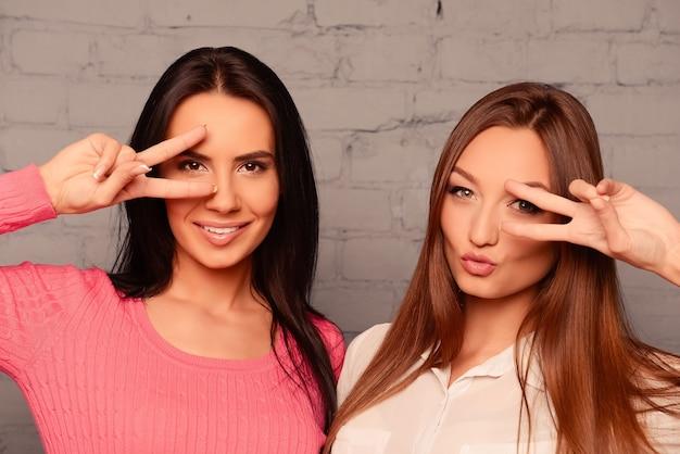 Twee grappig meisje gek rond en gebaren met vingers