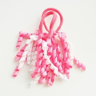 Twee grappige babyhaarbanden in de vorm van witte en roze spiraalvormige linten.