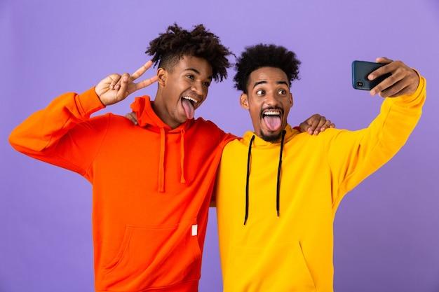 Twee grappige beste vrienden gekleed in kleurrijke hoodies