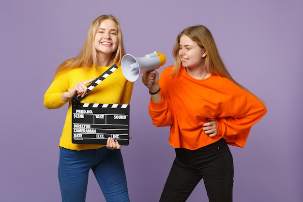 Twee grappige jonge blonde tweelingzusters meisjes houden klassieke zwarte film filmklapper, schreeuwen op megafoon geïsoleerd op violet blauwe muur. mensen familie levensstijl concept. .