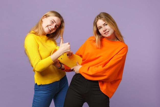 Twee grappige jonge blonde tweelingzusters meisjes in levendige kleding duim opdagen, gele skateboard geïsoleerd op violet blauwe muur houden. mensen familie levensstijl concept.