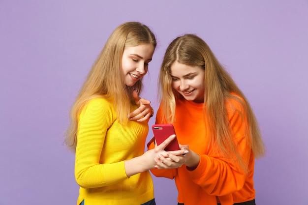Twee grappige jonge blonde tweelingzusters meisjes in levendige kleding met behulp van mobiele telefoon, sms-bericht typen geïsoleerd op pastel violet blauwe muur. mensen familie levensstijl concept.