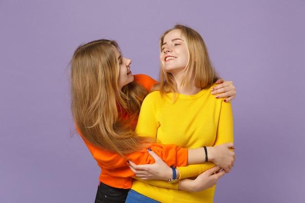 Twee grappige jonge blonde tweelingzusters meisjes in levendige kleurrijke kleding knuffelen, kijken naar elkaar geïsoleerd op pastel violet blauwe muur. mensen familie levensstijl concept.