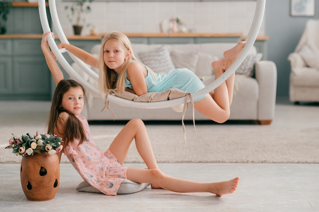 Twee grappige jonge meisjes in mooie jurken die schommeling berijden en in binnenlandse studio stellen.
