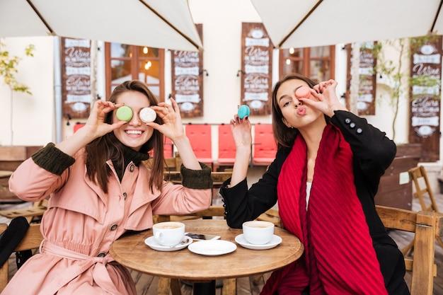 Twee grappige jonge vrouwen zitten en hebben samen plezier in het buitencafé