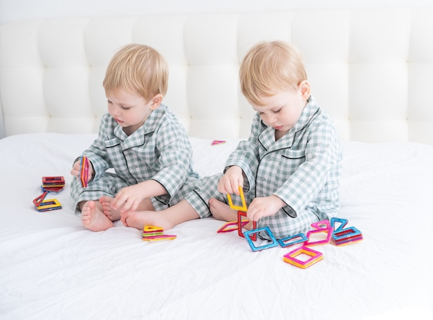 Twee grappige jongens broers tweeling op wit bed in pyjama's spelen in magnetische constructor