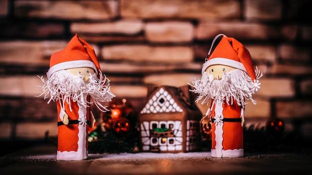 Twee grappige kerstman op de achtergrond van een peperkoekhuis..foto met kopieerruimte