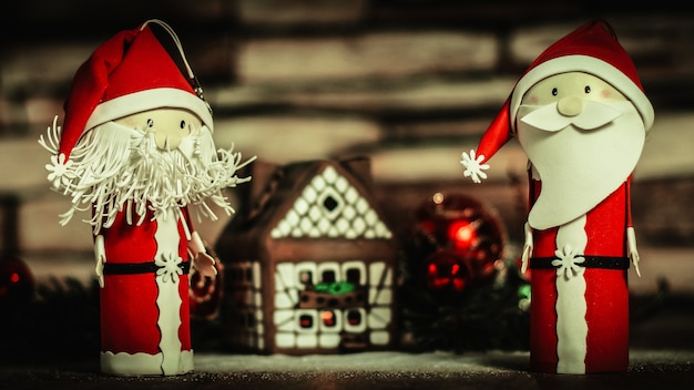 Twee grappige kerstman op de achtergrond van een peperkoekhuis.